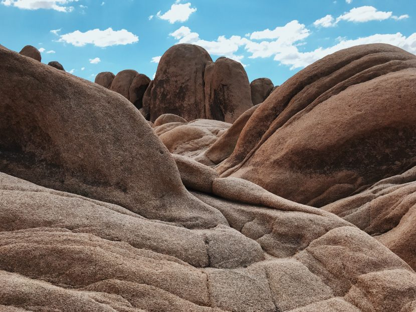 Standing at Arch Rock, looking at granite boulders with a blue sky.