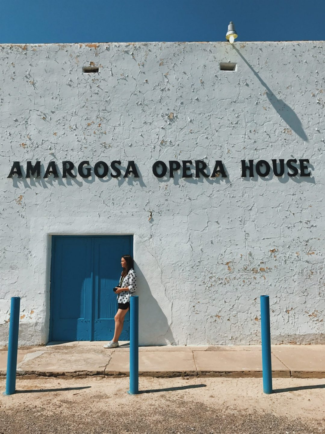 A girl leans against an old opera house with a blue door in the desert.