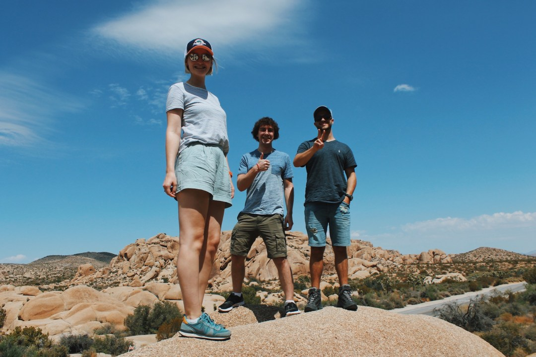 Three people stand on top of a huge layer of boulders at Joshua Tree National Park and smile at the camera.