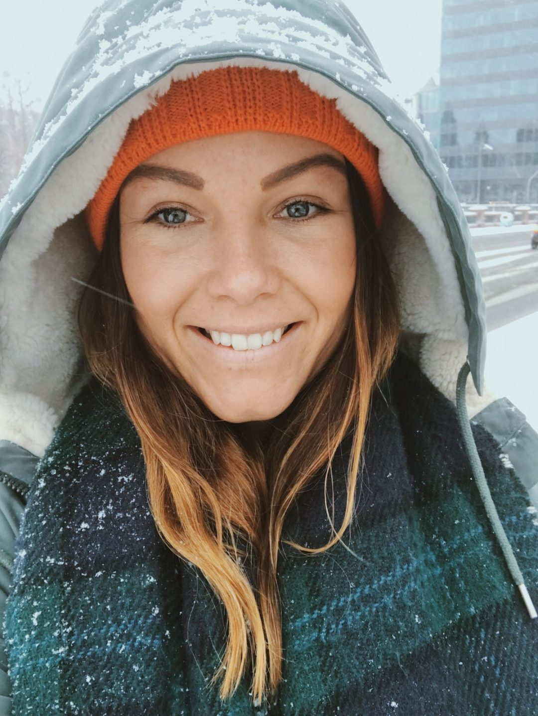 A girl smiling in the snow, wearing outdoor gear