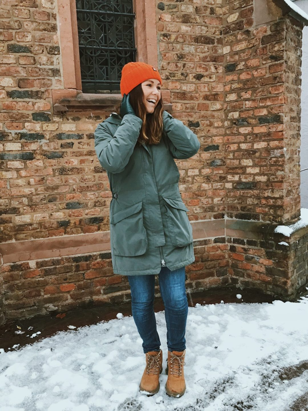 A girl standing on snow wearing hiking gear