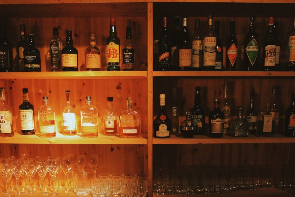A wooden bookcase full of alcohol and spirit bottles with glasses on the bottom shelf.