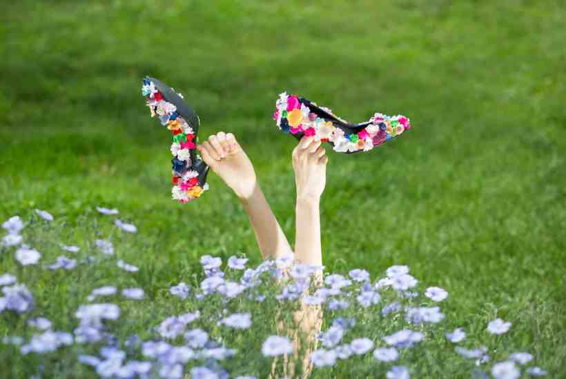 A woman laying in the grass with her flower heels in the air