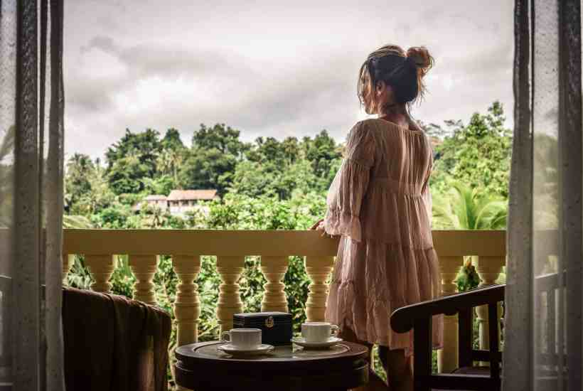 a woman gazing out the window at a jungle landscape