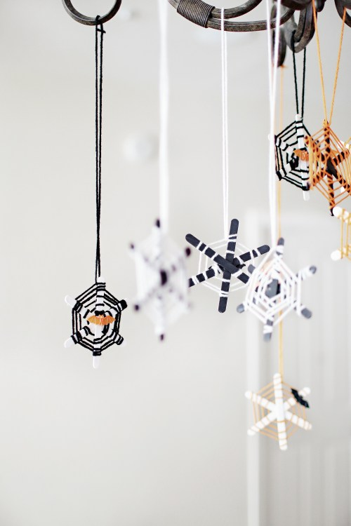 Halloween craft for the kids and these DIY Popsicle stick spiderwebs are the cutest! Our kiddos love hanging them up each year over our kitchen table. Catch the walk through over at Haus of Layne! #Halloween #HalloweenCraft #KidsCraftIdeas #HalloweenDecorIdeas #HalloweenIdeas