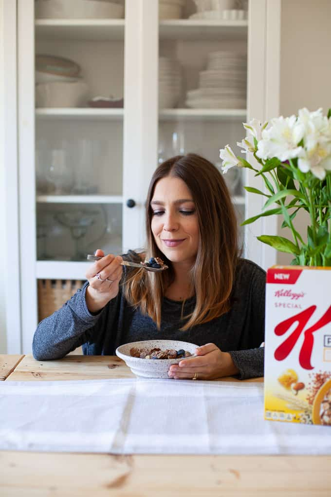 Woman smiling with bowl of Kellogg's cereal at hand
