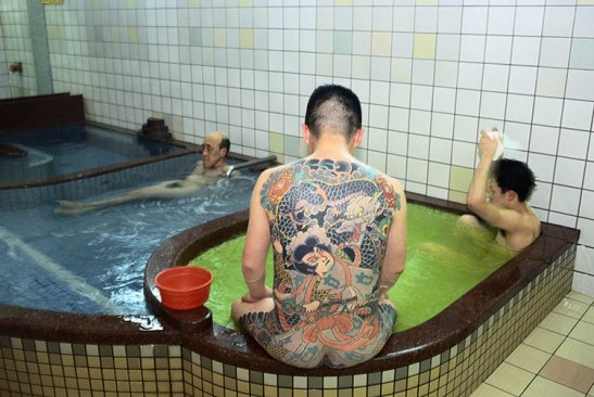 Kyoto, Japan --- A member of the Yakuza, or Japanese mafia, in a public bath. --- Image by © Gideon Mendel/Corbis