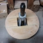 Placed on the frame, spun, and centered. Then, clamped on in place, turned over and screwed in (not shown)
