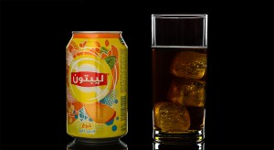 A cup with three ice cubes fill with Lipton Ice Tea with the can on the side
