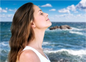 Woman profile portrait breathing deep fresh air on the beach with the ocean in the background Karen Lewis social worker new jersey overcome stress and anxiety
