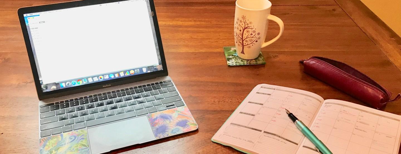 laptop, planner, pen and mug on desk