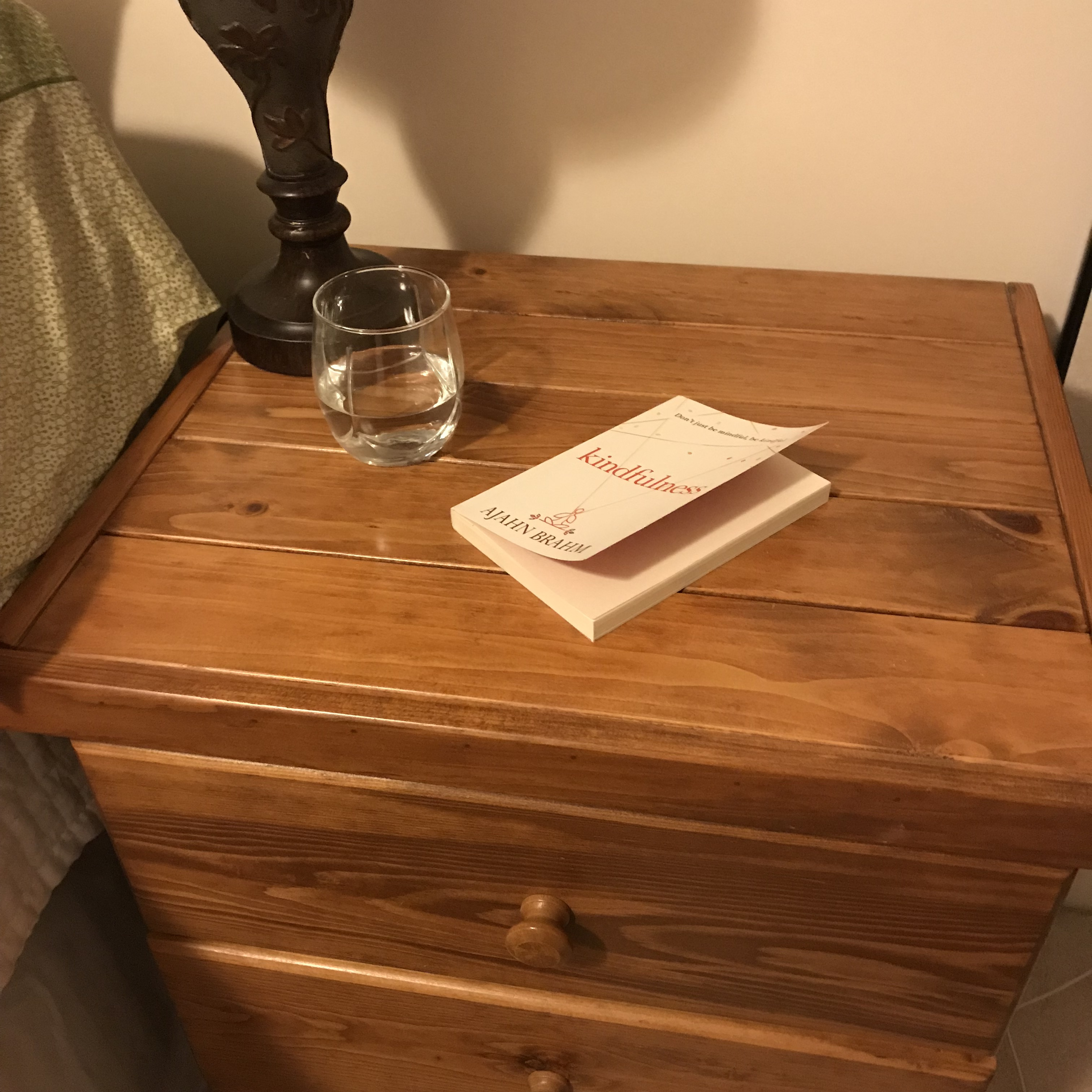 nightstand with glass of water, book, lamp