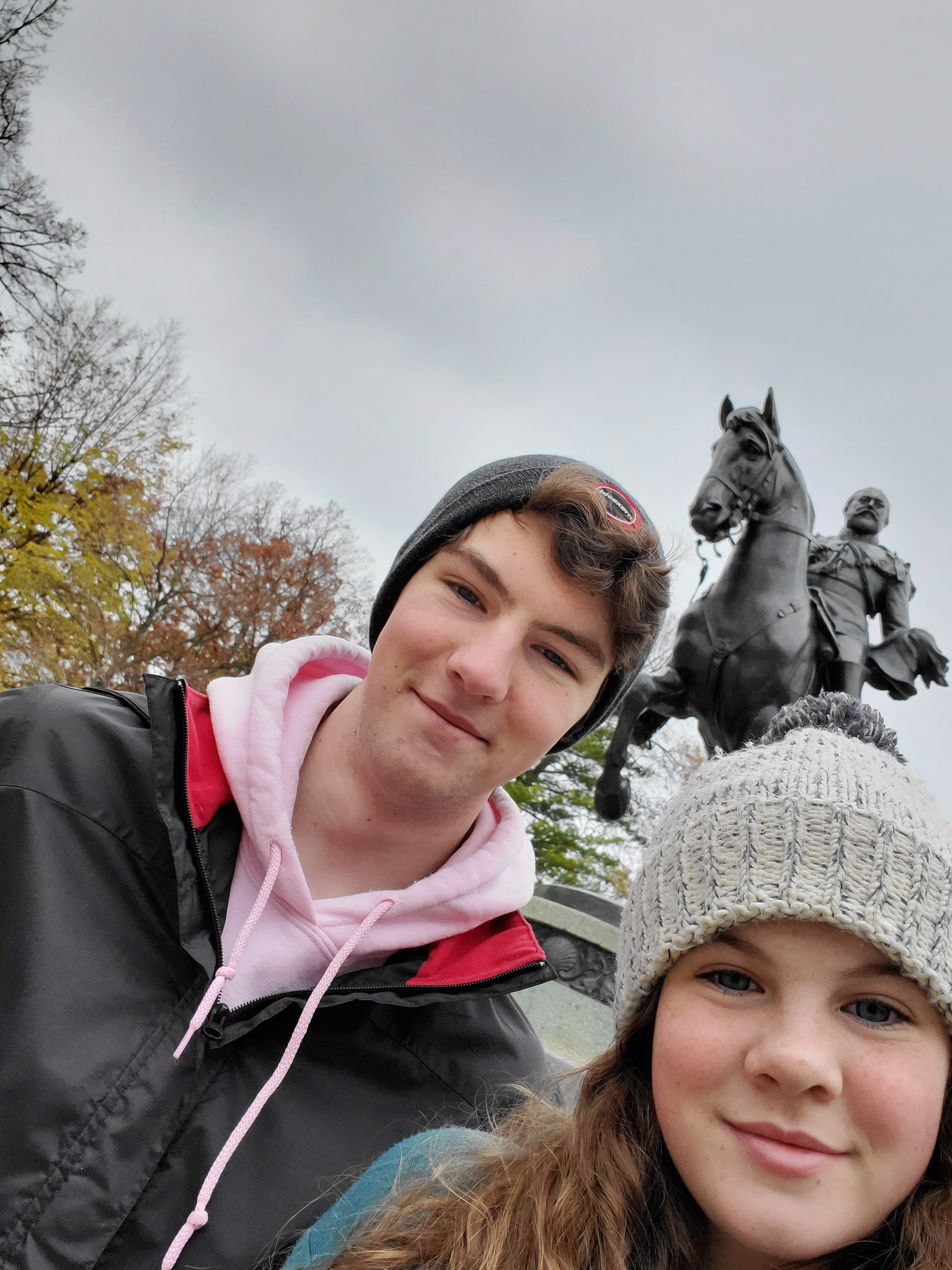 two teenagers with a statue in the background