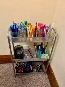 a shelf unit with many dozens of pens