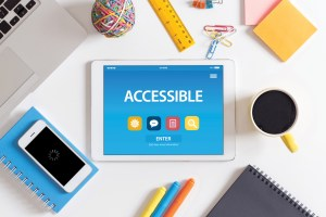 """desktop with office supplies and an iPad showing the word """"accessible"""""""