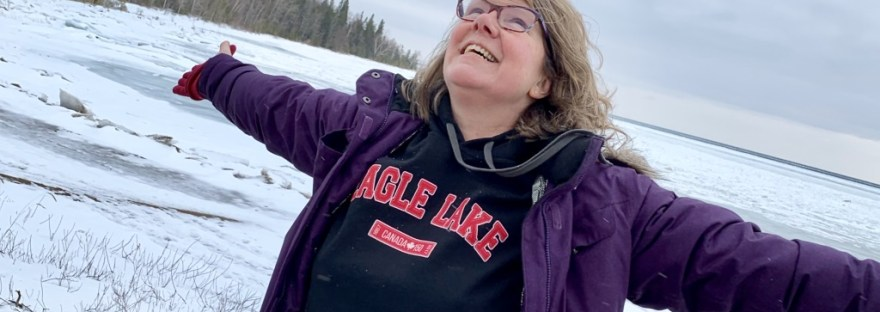 me with a big smile and arms wide looking up at the sky with a frozen lake in the background