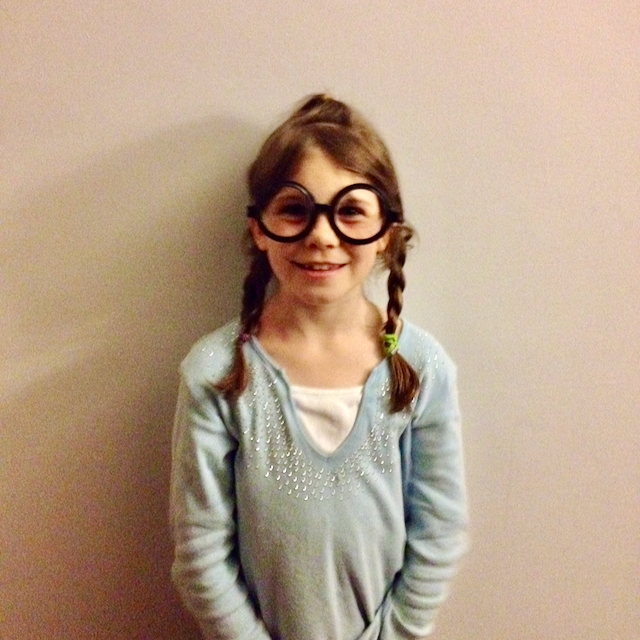 young girl wearing comically large glasses and smiling