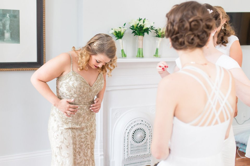 Bride getting dressed in champaign vintage BHLDN gown in shotgun house in New Orleans by Karen Shoufler