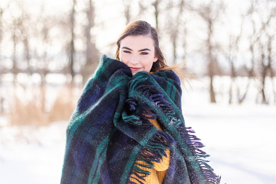 Senior girl in the snow wrapped in a blanket