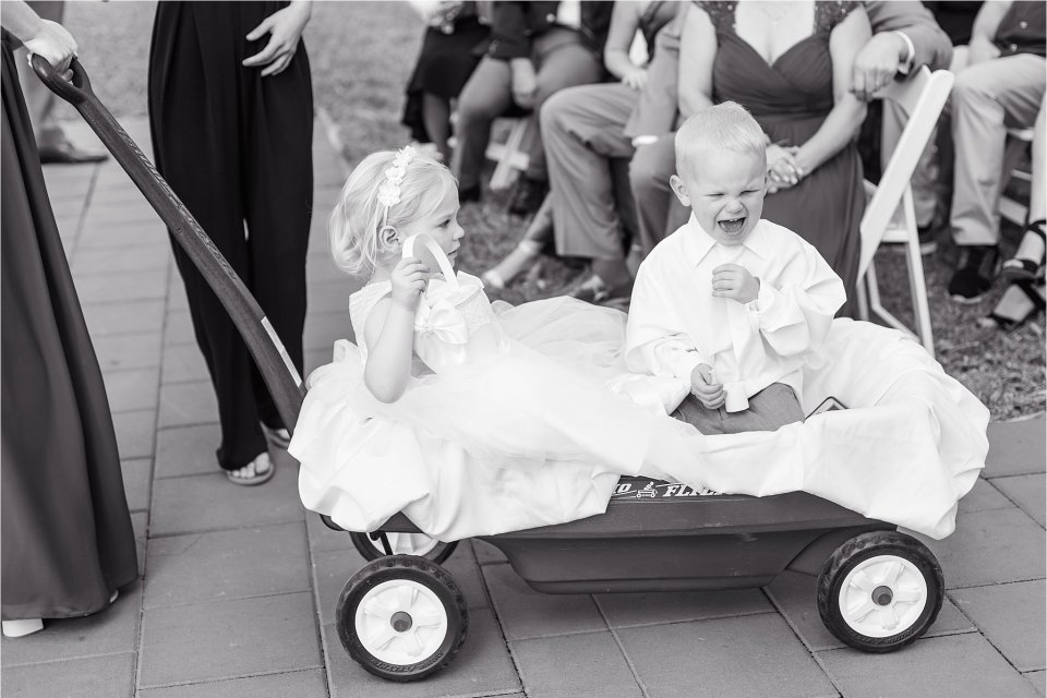 Flower girl and crying ring bearer at Spring wedding ceremony outside at Heitman House in downtown Ft Myers, Florida wedding venue