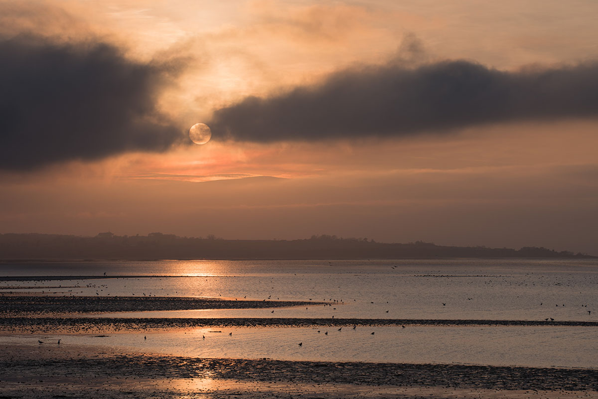 Black Isle photography - the sun, between two bands of cloud, setting over a bay of water with birds on the surface