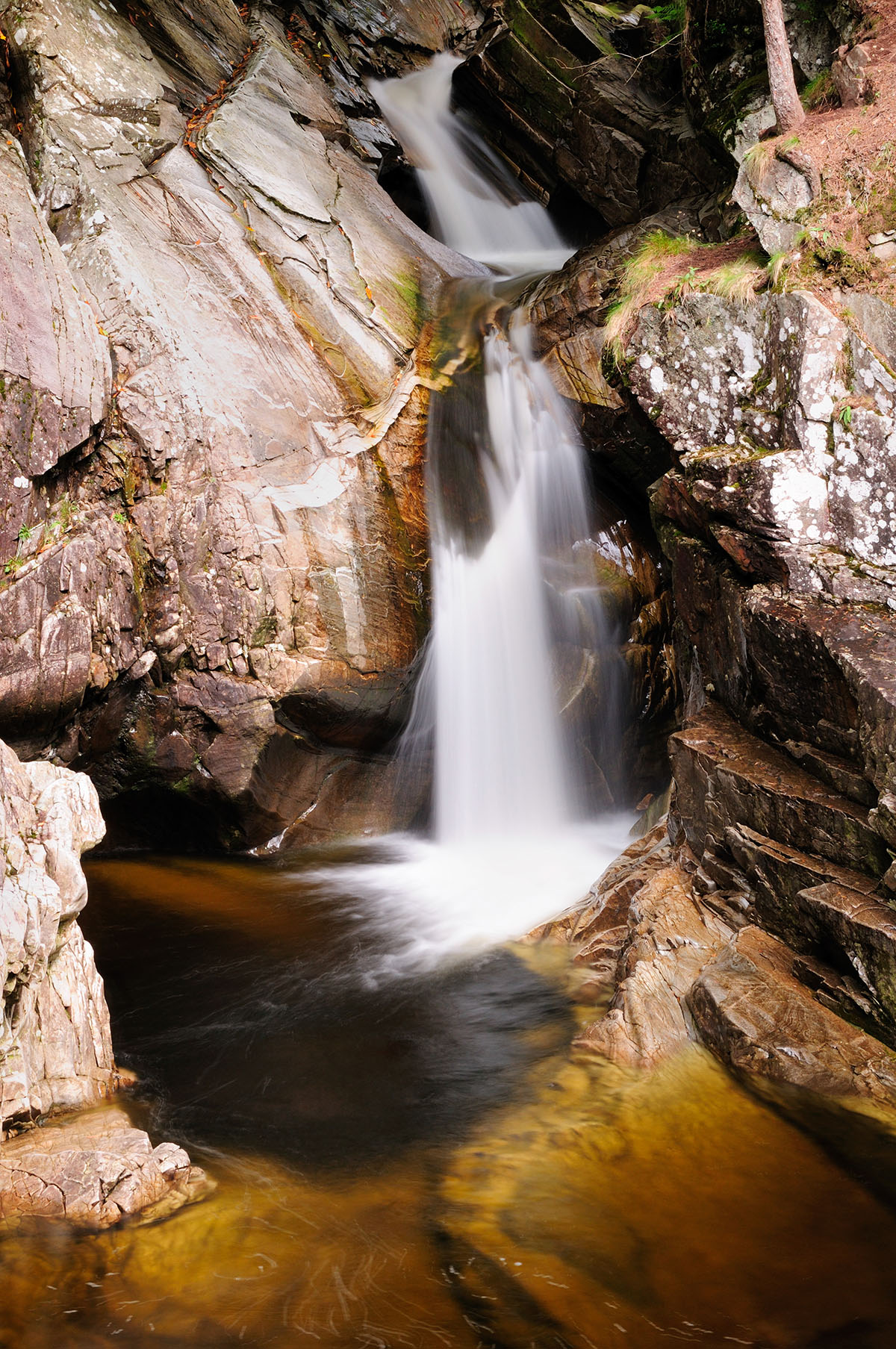 Waterfall photographed in slow motion, in a small gorge with smooth grey rocks on either side and dark pool at the base