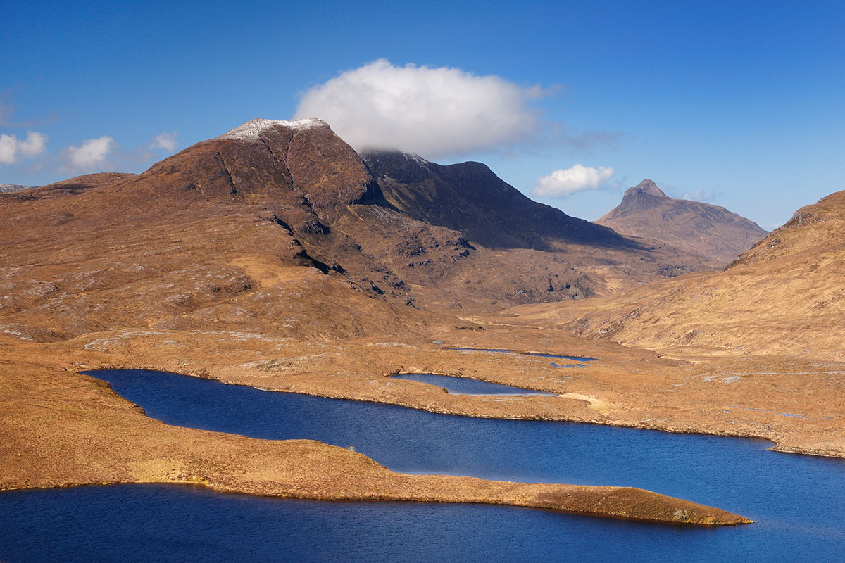 Mountains with a dusting of snow on the summit with a single white cloud in a blue sky, above moorland and small lakes