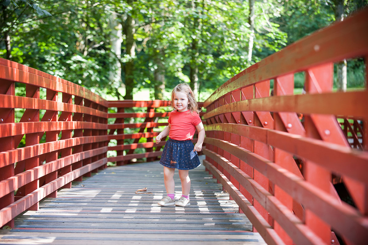Young girl wearing an orange t-shirt and navy skirt standing on a wooden bridge with trees in the background