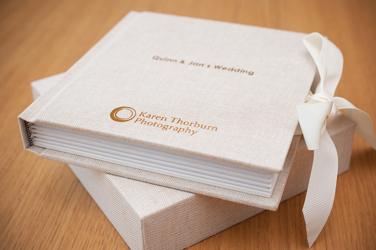 Wedding FAQS - closed square wedding album with an oatmeal linen cover and gold embossed lettering on an oak table