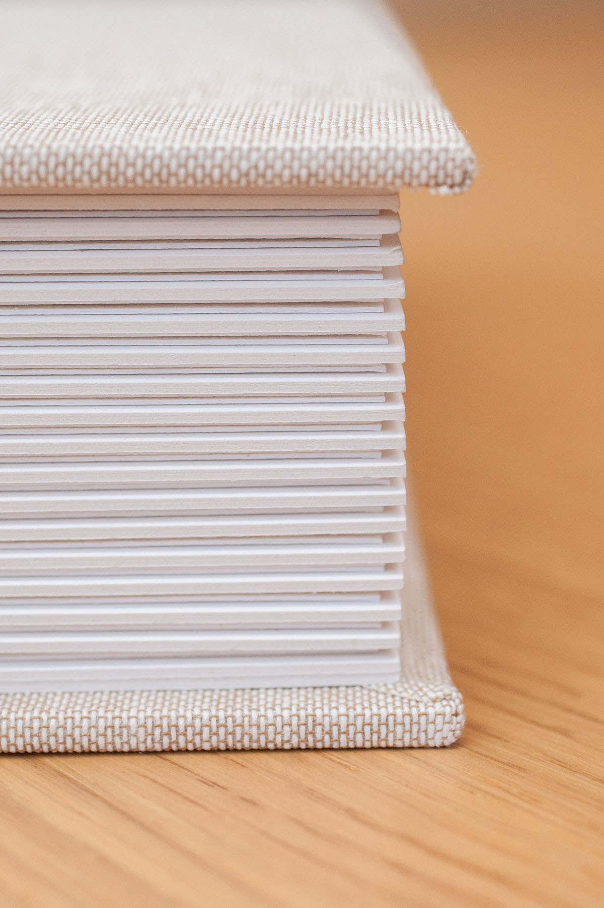 Detailed photo showing a side on view of a luxury matted wedding album, with the pages closed, and an oatmeal linen cover.