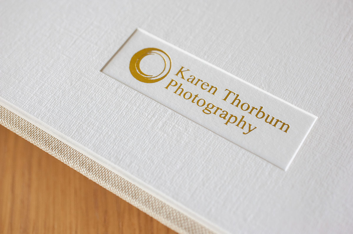 Detailed image showing the Karen Thorburn Photography logo in gold lettering embossed on an inside page of a wedding album.