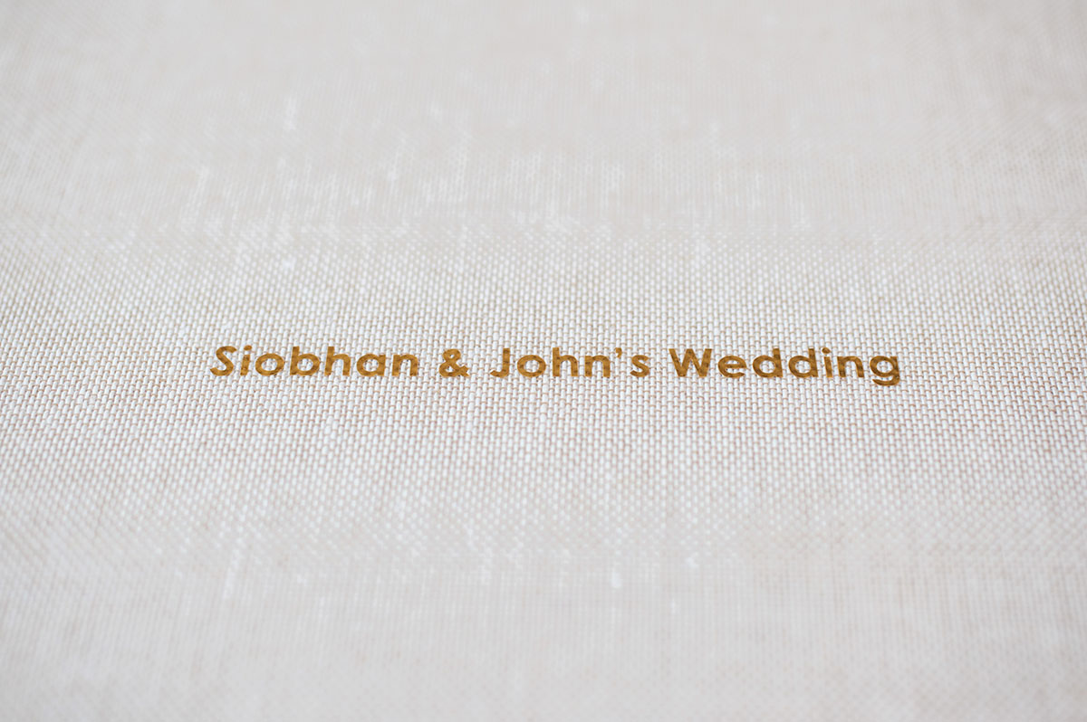 Close-up photo showing the text 'Siobhan & John's Wedding' in gold lettering on the front of an album with a linen cover.