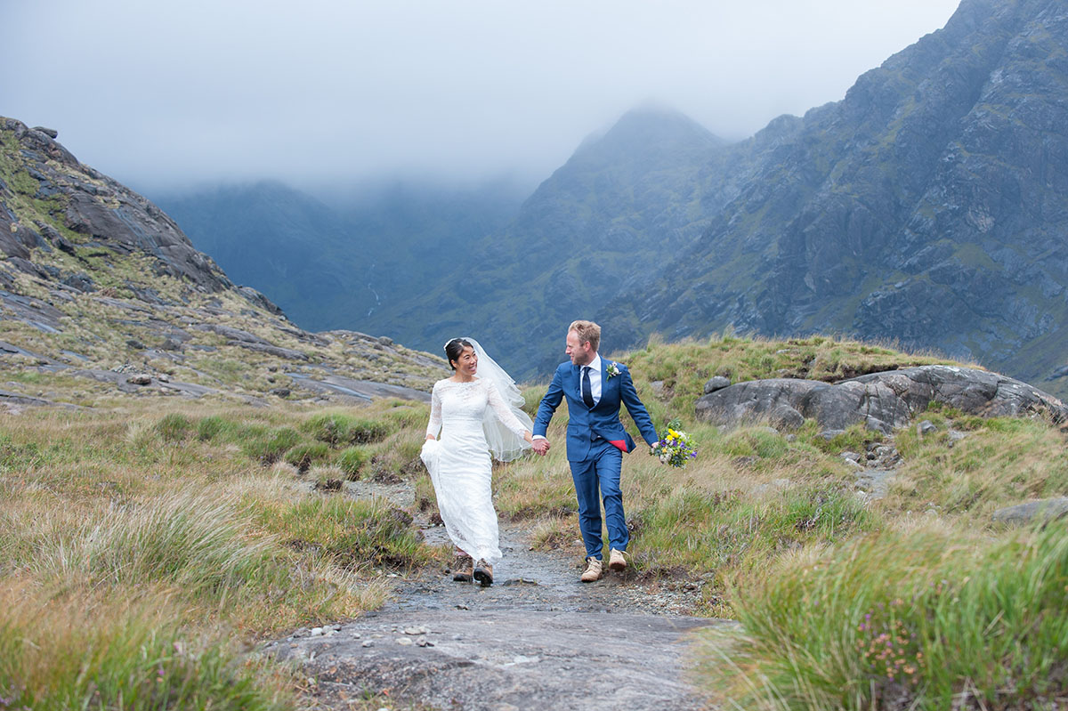 Wedding photo gallery - bride and groom holding hands and smiling, walking on a rock next to grass in front of mountains