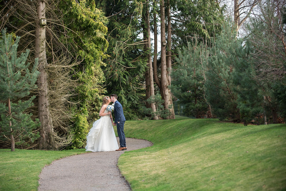 Wedding photography - bride and groom standing on a path and kissing with tall trees above them and grass next to the path