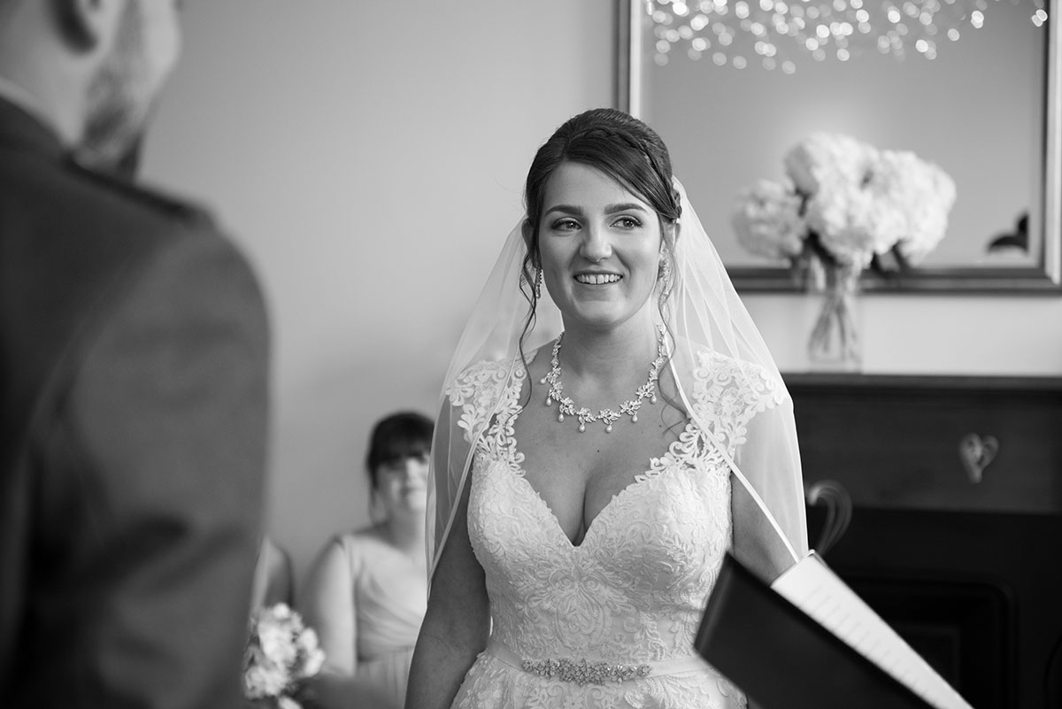 Wedding photography portfolio - monochrome image of a bride standing in front of a mirror smiling during her wedding ceremony