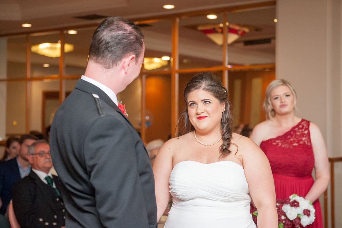 Wedding photography portfolio - bride standing in front of a bridesmaid in a white dress with the bride smiling at the groom