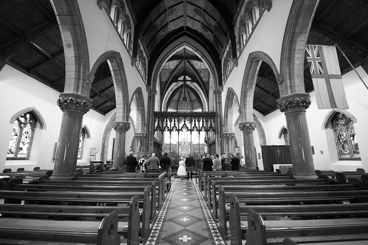 Wedding photography portfolio - monochrome symmetrical image of the inside of a large cathedral with a wedding taking place