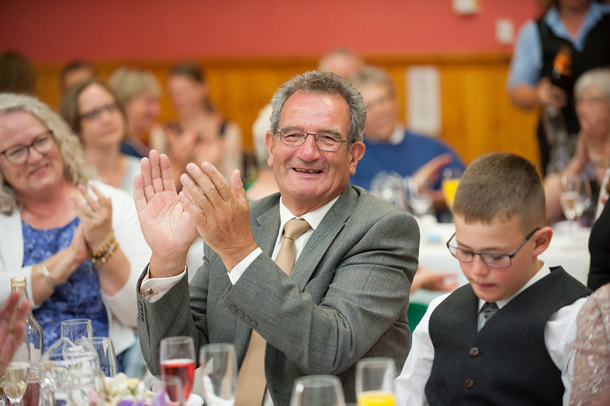 Wedding photos - candid image of a male wedding guest in a grey suit and brown tie smiling and applauding