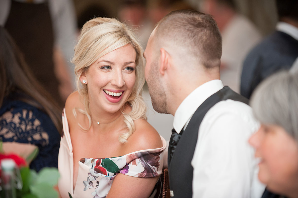 Wedding pictures - woman with blonde hair and a floral dress looking at her male partner and laughing at a wedding reception
