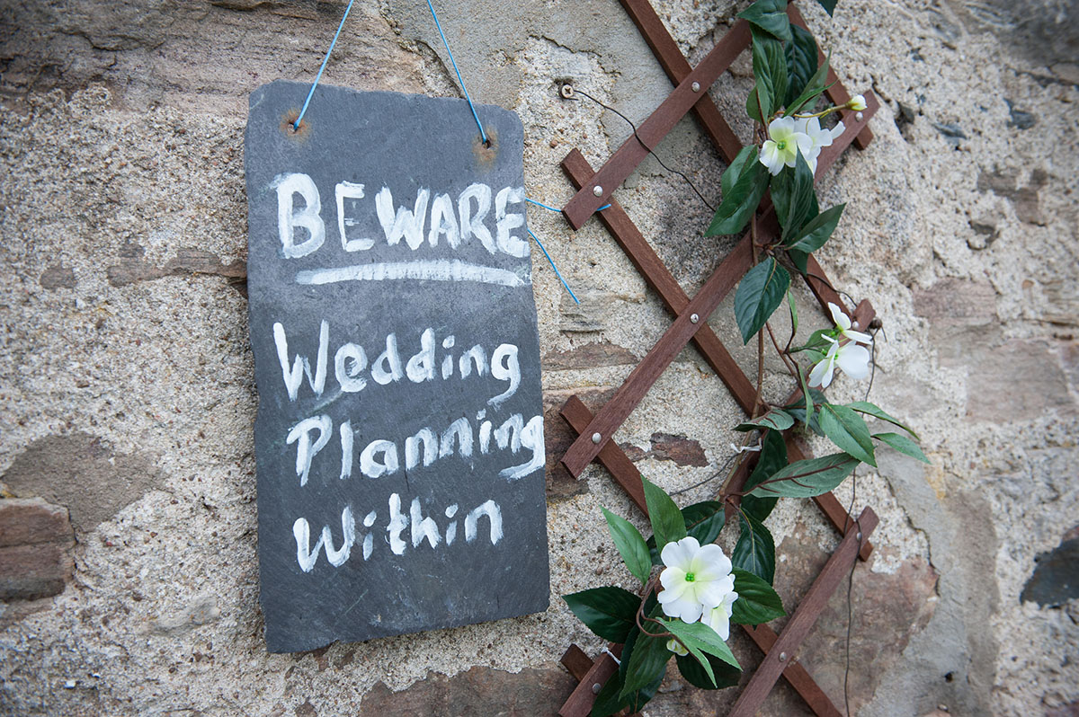 Wedding portfolio - small blackboard with the text 'BEWARE Wedding planning within' hanging next to flowers on outside wall