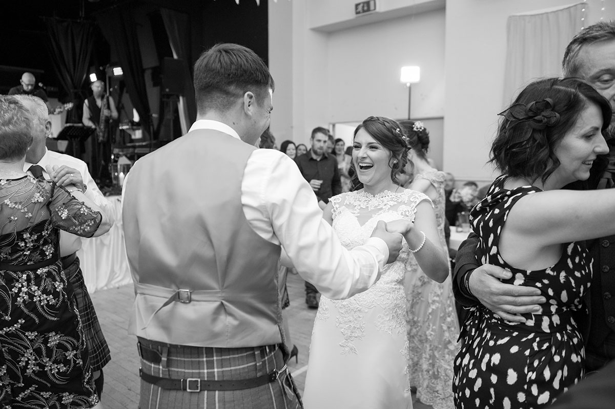 Wedding portfolio - monochrome image of a bride laughing as she dances with her groom who has his back to the camera