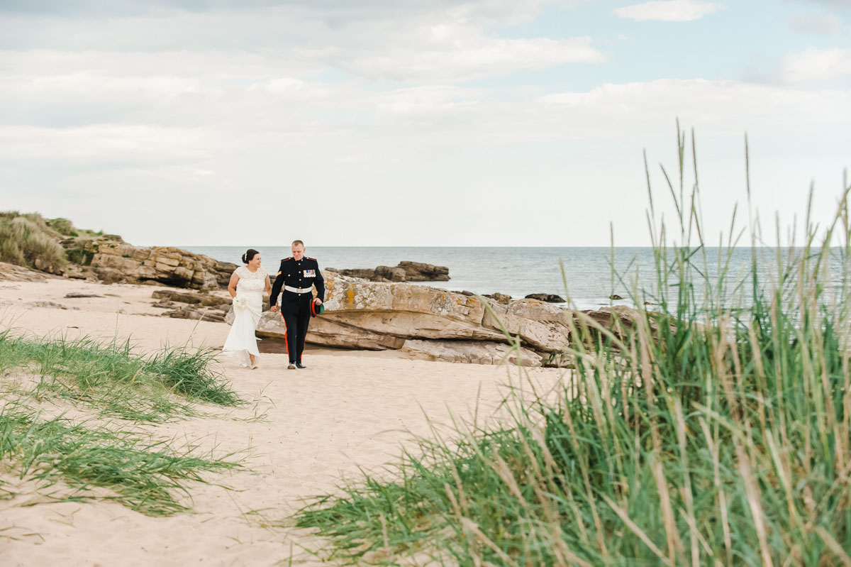 A bride and groom walking hand in hand on a sandy beach in front of rocks with the sea beyond, and grass in the foreground