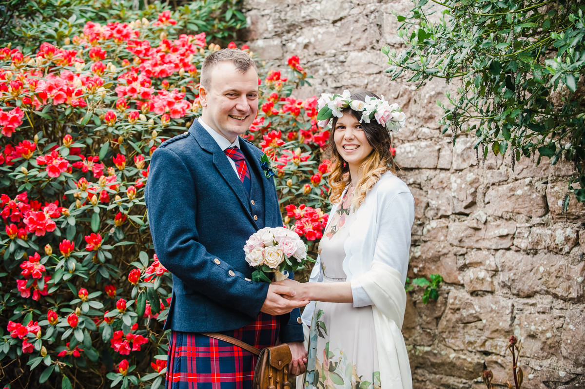 A bride with flowers in her hair, holding a bouquet, beside her groom in front of a stone wall and a bush with red flowers