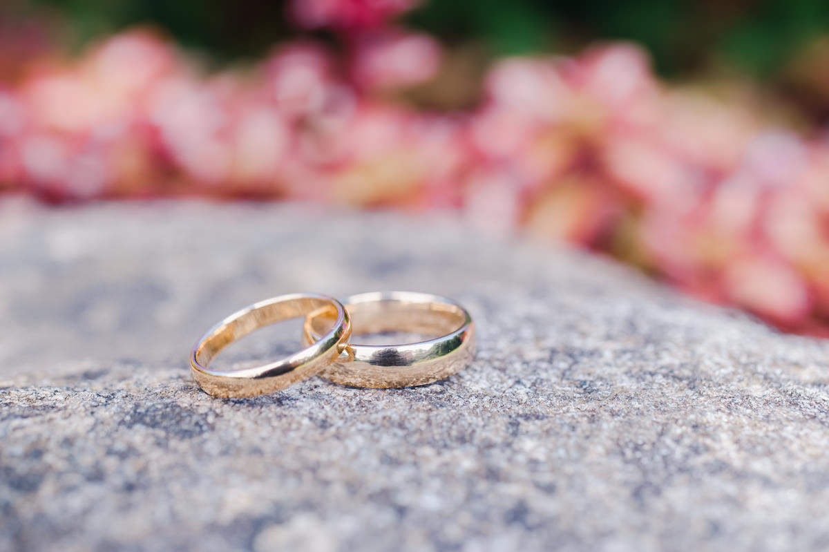Matching gold wedding rings on a granite rock with soft focus pink flowers in the background