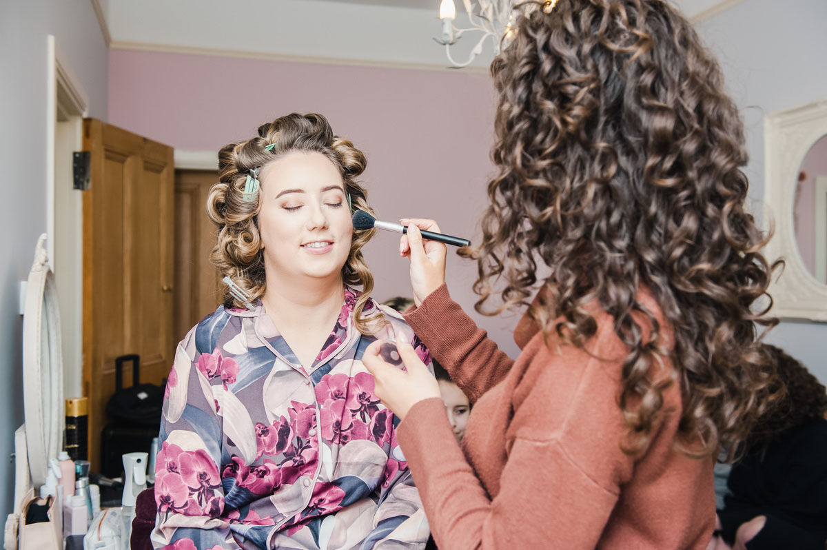 A woman wearing flowery pyjamas with curlers in her hair, smiling as another woman applies makeup to her cheek
