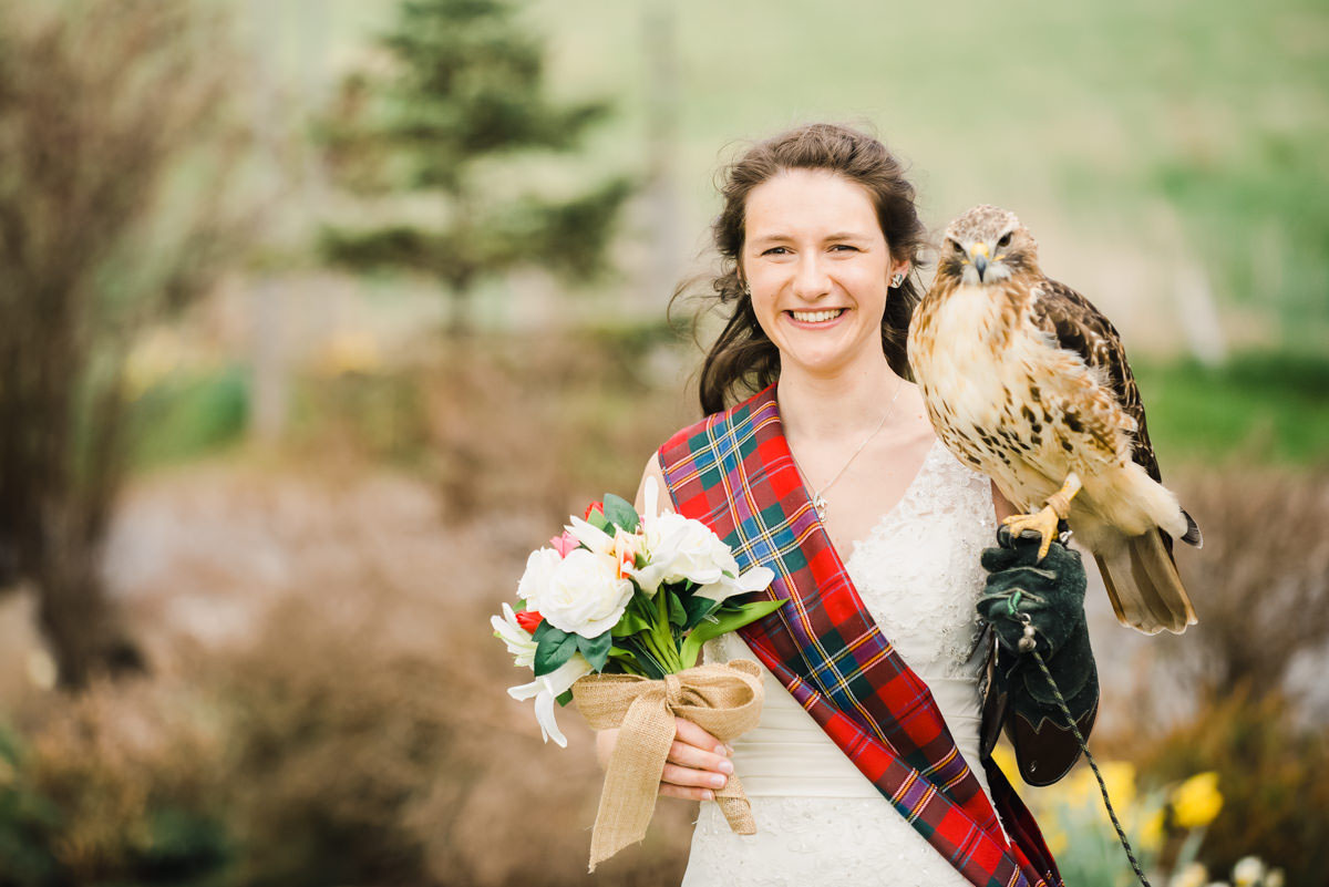 A wedding photo of a bride wearing a tartan sash over a white dress and holding flowers and a bird of prey