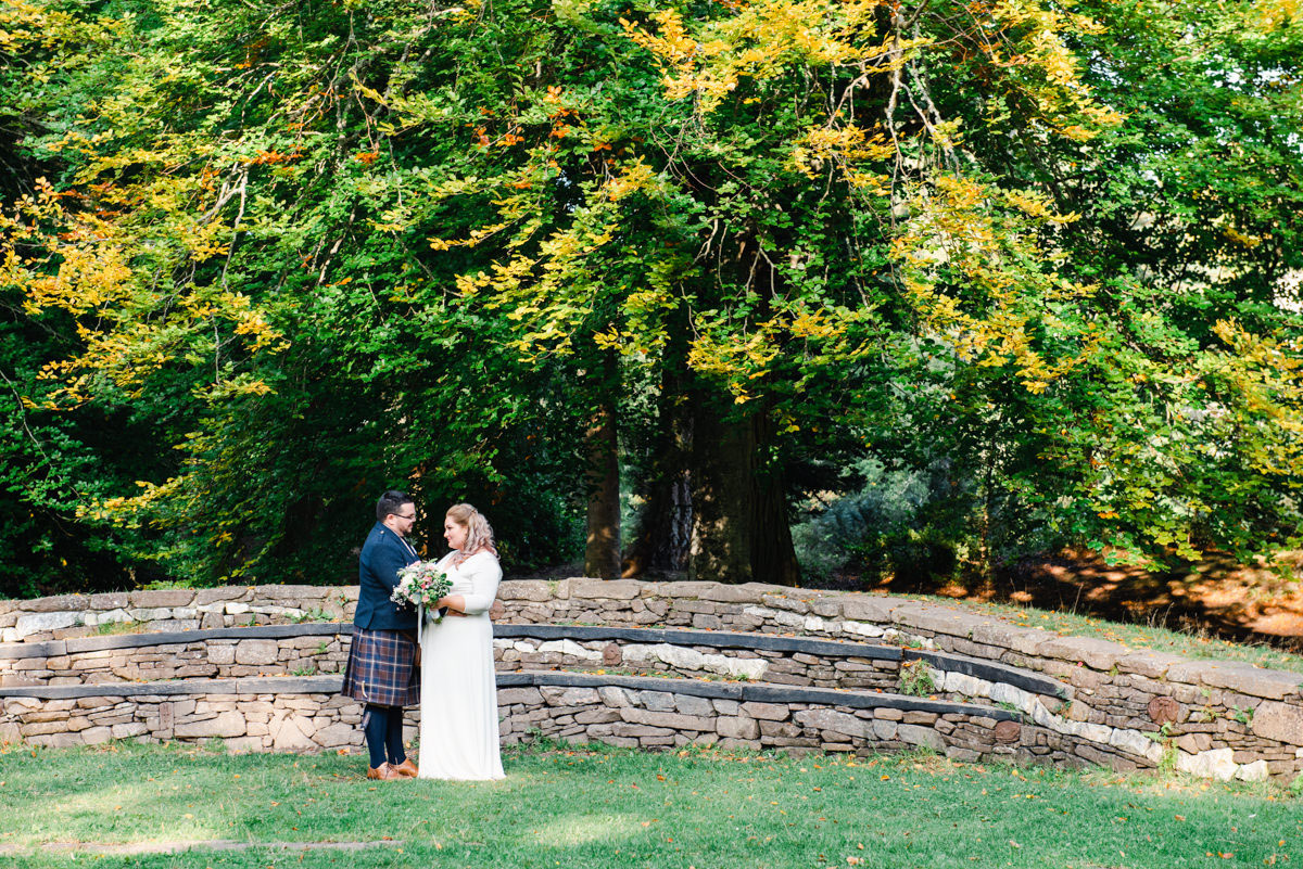 A bride and groom holding flowers and standing facing each other in front of a curved stone wall below mature green trees