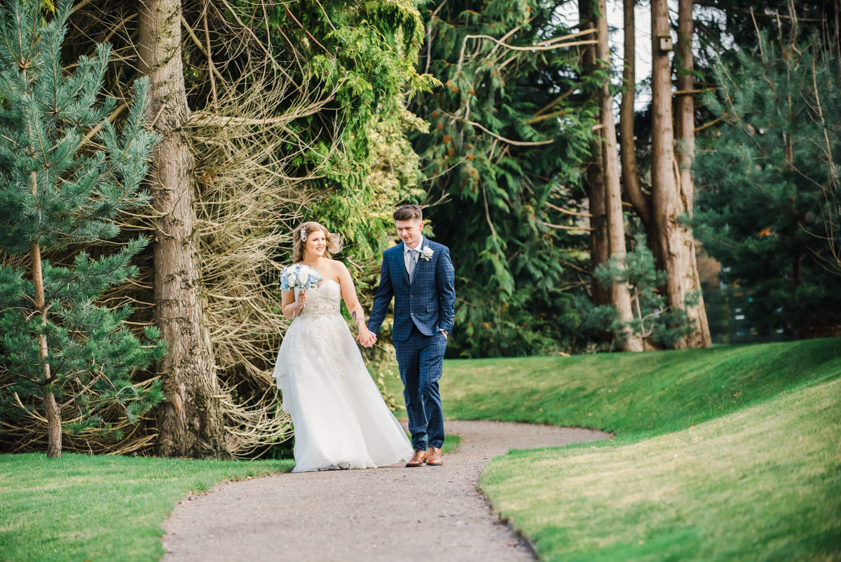 A bride and groom holding hands and walking on a curved path with grass on either side and tall trees in the background
