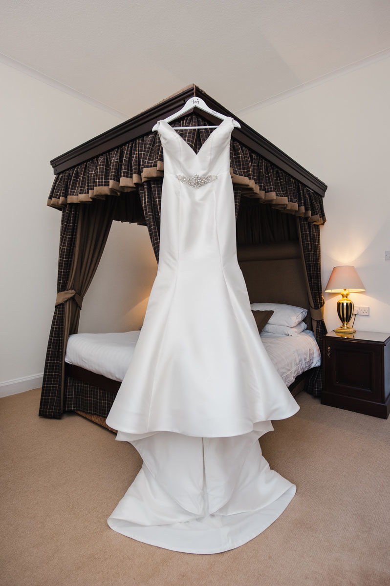 Wedding photo of a white silk wedding dress hanging on the end of a brown four poster bed in a room with a pale pink carpet
