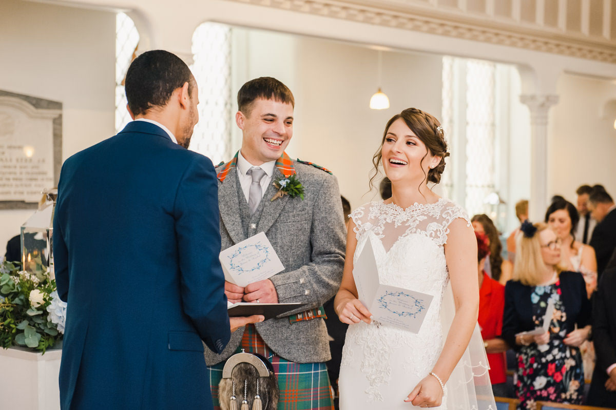 Wedding photograph of a bride and groom laughing during their church ceremony, with the groom facing his bride